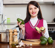 Smiling woman with avocado. In home kitchen Stock Photography