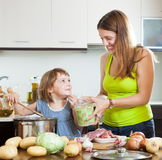 Smiling woman with baby cooking Royalty Free Stock Photos