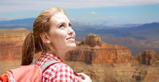 Smiling woman with backpack over grand canyon Stock Photos
