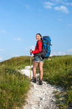 Smiling woman with backpack and trekking poles on the mountain t Royalty Free Stock Photography