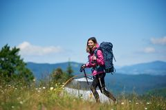 Woman hiker near camping in the mountains with backpack and trekking sticks in the morning. Smiling woman backpacker with backpack and trekking sticks near tent Royalty Free Stock Images
