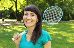 Smiling woman with badminton racket in the summer park Stock Image