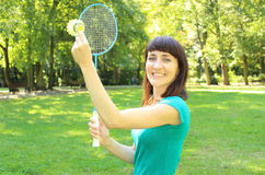 Smiling woman with badminton racket in the summer park Royalty Free Stock Photo