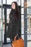 Smiling woman with bag enters door Stock Photos
