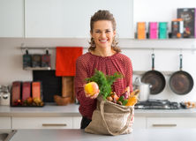 Smiling woman with bag of fresh produce holding up an apple Stock Image