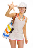 Smiling woman with bag showing starfish Stock Photography