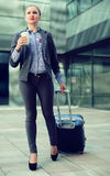 Smiling woman with baggage and coffee Stock Image