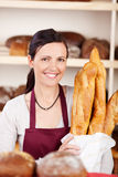 Smiling woman with baguettes Royalty Free Stock Photo