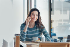 Smiling woman at the bar having a phone call Stock Photography