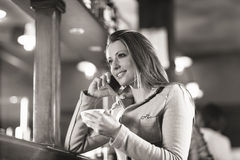 Smiling woman at the bar having a phone call Royalty Free Stock Photography