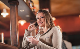 Smiling woman at the bar having a phone call Royalty Free Stock Photo