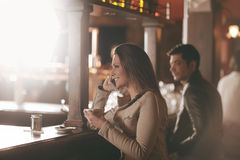 Smiling woman at the bar having a phone call Stock Photos