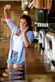 Smiling woman at the bar talking on mobile Stock Image