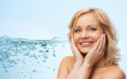 Smiling woman with bare shoulders touching face. Beauty, moisturizing, people and skincare concept - smiling woman with bare shoulders touching face over blue Stock Images