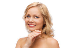 Smiling woman with bare shoulders touching face Royalty Free Stock Photos