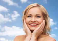 Smiling woman with bare shoulders touching face Stock Image
