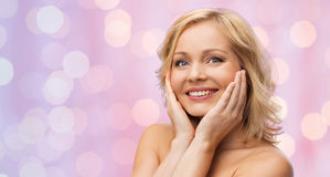 Smiling woman with bare shoulders touching face Stock Photo