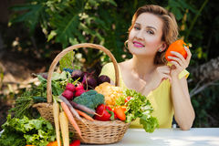 Smiling woman with basket full of vegetables outdoors. Healthy lifestyle. Stock Images