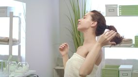 Smiling woman in bath towel making hair tail front mirror in bathroom stock video
