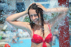 Smiling woman bathes in pool under water splashes. Smiling beautiful woman bathes in pool under water splashes, holding hands behind head Stock Image