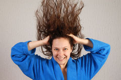 Smiling woman in bathrobe with flying wet hair Stock Images