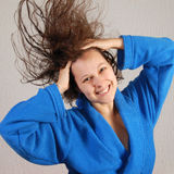 Smiling woman in bathrobe with flying wet hair Royalty Free Stock Image