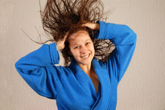 Smiling woman in bathrobe with flying wet hair Stock Photography