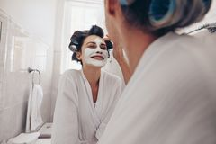 Smiling woman in bathrobe getting her facial done at home. Two women standing in bathroom with curly rollers pinned on hair. Smiling women in bathrobe getting royalty free stock photos