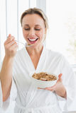 Smiling woman in bathrobe having cereal Stock Image