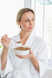 Smiling woman in bathrobe having cereal Stock Photos
