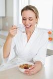 Smiling woman in bathrobe having cereal Stock Photos