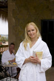 Smiling woman in bathrobe holding books on patio Stock Images