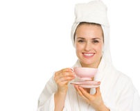 Smiling woman in bathrobe holding cup of coffee Stock Photography