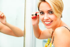 Smiling woman in bathroom applying mascara Stock Photography