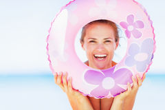 Smiling woman on beach looking through swim ring Royalty Free Stock Photo