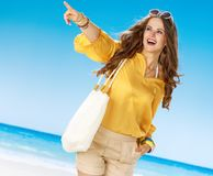 Smiling woman on beach pointing at something. Perfect summer. smiling woman in shorts and yellow blouse with white beach bag on the beach pointing at something Royalty Free Stock Photos