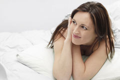Smiling woman on bed. Young woman in her late 20's - early 30's resting and smiling on bed.White linings and horizontal frame stock photos