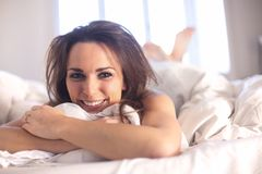 Smiling Woman on Bed Stock Photo