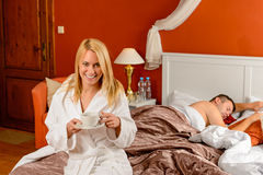 Smiling woman bed drinking boyfriend sleeping Royalty Free Stock Photography