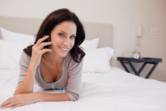 Smiling woman on the bed having a phone call Stock Images