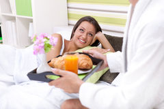Smiling woman in bed with her boyfriend serving breakfast Stock Photo