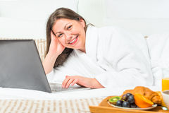 Smiling woman in bed with a laptop Royalty Free Stock Photography
