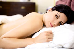 Smiling woman in bed naked Royalty Free Stock Images