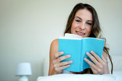 Smiling woman in bed reading a book Royalty Free Stock Photography