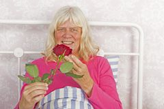 Smiling woman in bed with rose Royalty Free Stock Photo