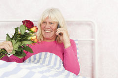 Smiling woman in bed with roses and telephone Stock Photo