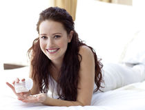 Smiling woman in bed taking pills Royalty Free Stock Photography