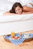 Smiling woman in bed watching homemade breakfast. Smiling woman in white bed watching homemade breakfast Stock Photo