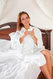Smiling woman in bedroom drinking coffee on bed Royalty Free Stock Photography