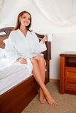 Smiling woman in bedroom drinking coffee on bed Royalty Free Stock Photo